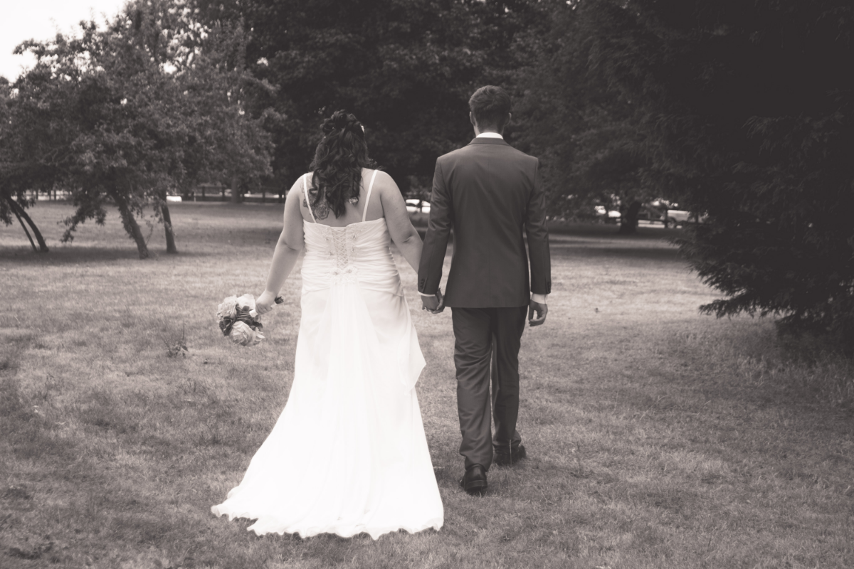 black and white bride and groom walking in garden